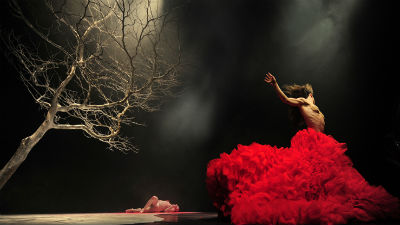 A dancer in a long red dress dances in front of a bare tree on a darkly lit stage.