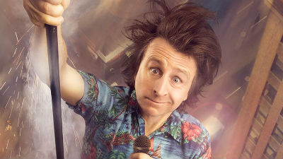 Comedian Milton Jones holds a microphone while appearing to be sliding down the side of a skyscraper.