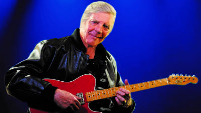 Marty Wilde sits and holds his guitar on a brightly lit stage.