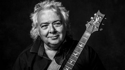 A black and white close up of Bernie Marsden holding a guitar.