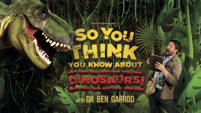 Dr Ben Garrod looks shocked as he looks up at a model of a T-Rex.