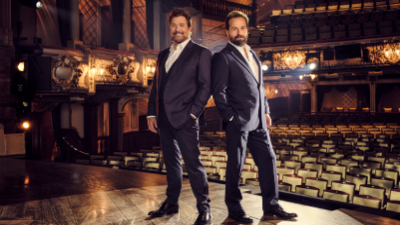 Michael Ball and Alfie Boe standing on a well-lit stage with an empty audotorium in the abckground.