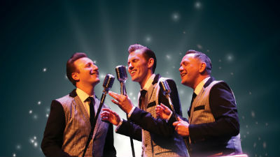 Three 50s style crooners stand around a vintage microphone.