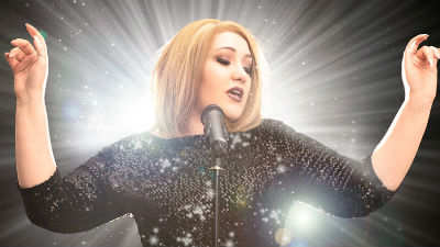 Christina Rogers as singer Adele, wearing black as she stands in front of a microphone.
