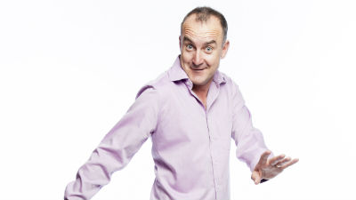 Comedian Jimeoin in a pale pink shirt against a white background.
