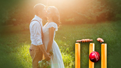 A couple embrace in a field. In the foreground a cricket ball and wicket.