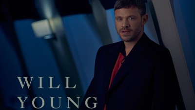 Singer Will Young in a dark suit leans against a wall with the white text 'Will Young'