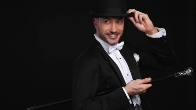 Dancer Giovanni Pernice wears a a black and white tux and tips his hat whilst holding a cane.