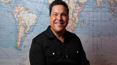 Comedian Dom Joly smiles as he stands in front of a map of the world.