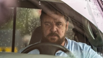 Russell Crow looking angry as he sits in a car in a still from Unhinged.
