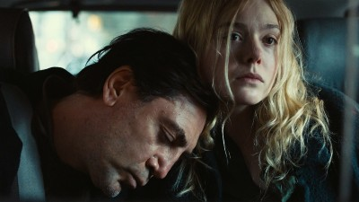 Javier Bardem rests his head on Elle Fanning's shoulder in a still from The Roads Not Taken.