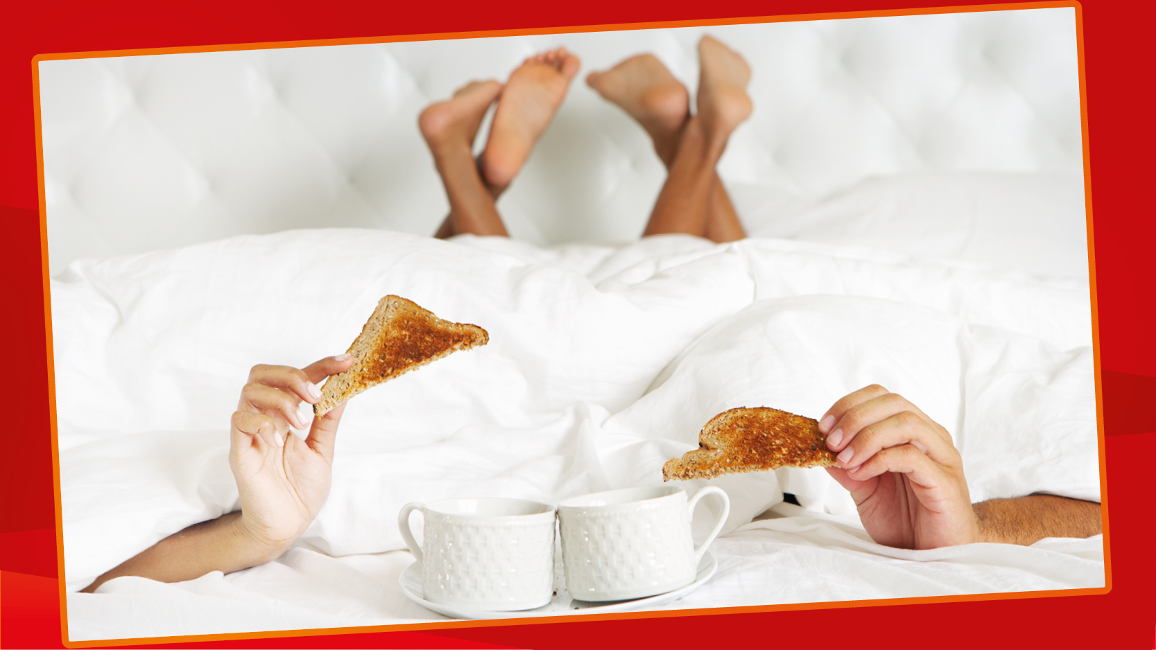 A couple lie under white covers in bed, hands holding toast triangles poking out at the bottom.