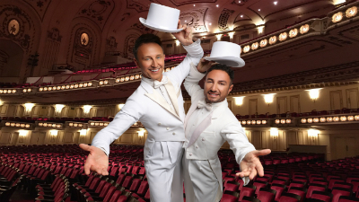 Ian Waite and Vincent Simone wear white tuxedos and top hats as they stand on a stage with an empty auditorium behind them.