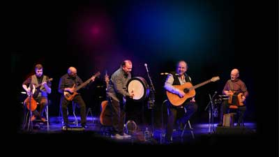 The Fureys syand on a well lit stage with their instruments.