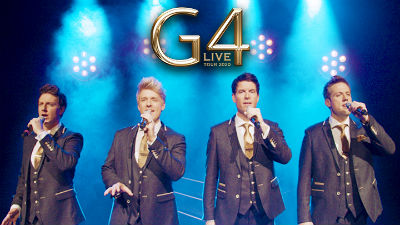 G4 stand on stage wearing suits, with bright blue stage lights in the ackground and gold lettering reading 'G4'