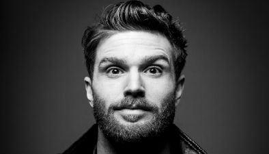 A black and white close up of comedian Joel Dommett.