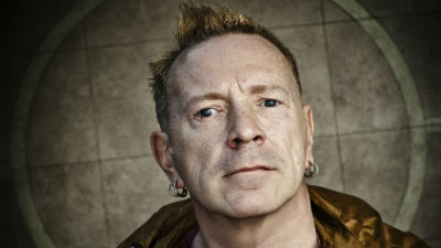 A close up of John Lydon against a dark background.