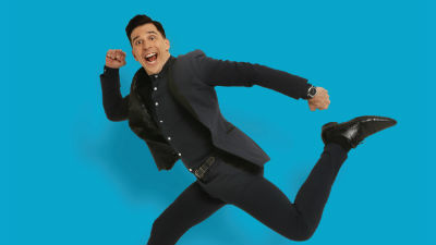 Comedian Russell Kane in a running pose against a bright blue background.