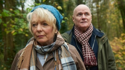 Dave Johns and Alison Steadman wrapped up in warm coats and scarves as they walk in woods in a still from the film 23 Walks.