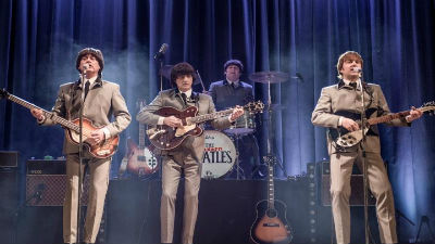 The Cavern Beatles stand on a stage wearing beige suits and holding their instruments.
