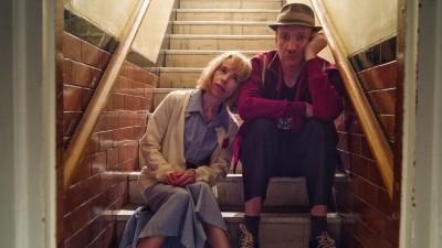 Sally Hawkins and David Thewlis sit at the bottom of a flight of stairs in a still from Eternal Beauty movie.