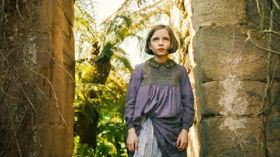 Dixie Egerickx stands in an archway of a garden in a still from the film 'The Secret Garden'