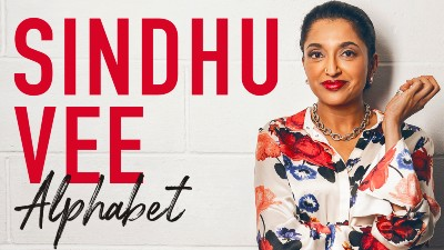 Comedian Sindhu Vee wears a floral shirt and stands agasint a white brick background. Large red text to the left reads 'Sindhu Vee', beneath it black text reads 'Alphabet'