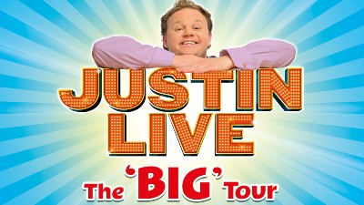 Children's TV star Justin Fletcher stands against a bright blue background with large letters reading 'Justin Live the Big Tour'